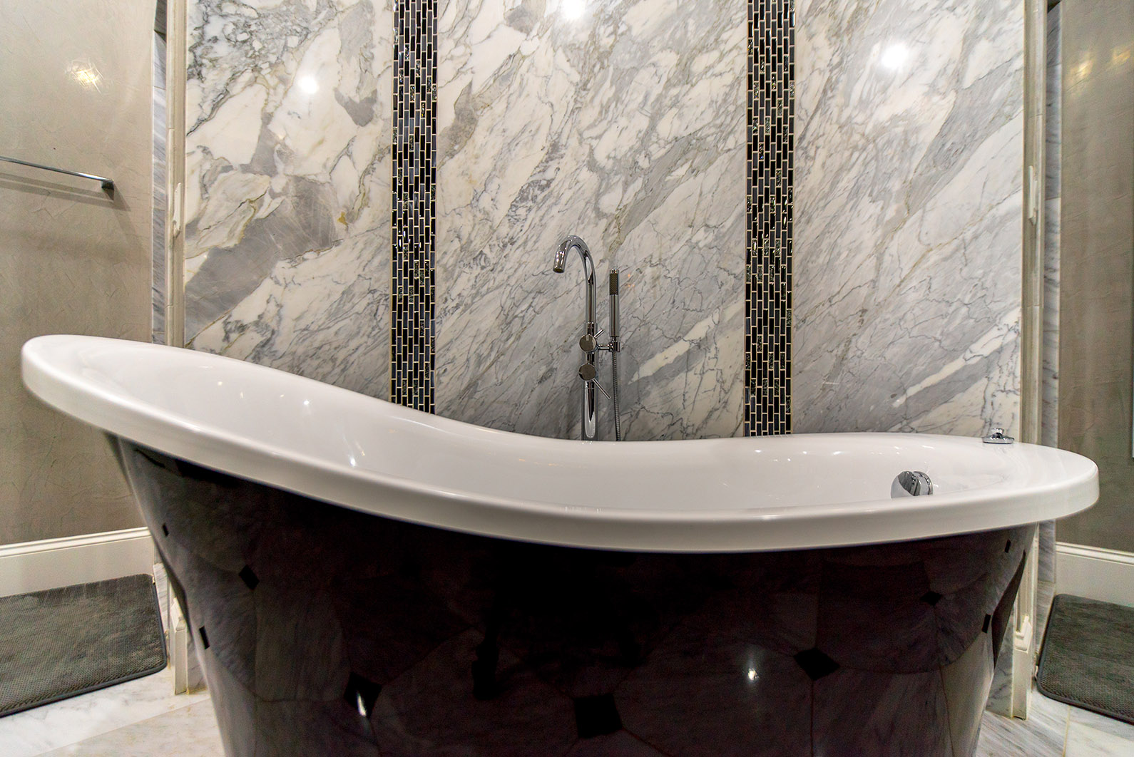 Comfortable bath area accented with a floor to ceiling Super White marble wall
